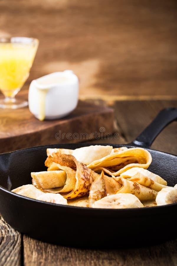 Crêpes avec les bananes et la sauce crème à caramel photographie stock libre de droits