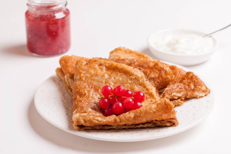 Crêpes avec les groseilles rouges et la crème sure d'un plat d'isolement photo stock