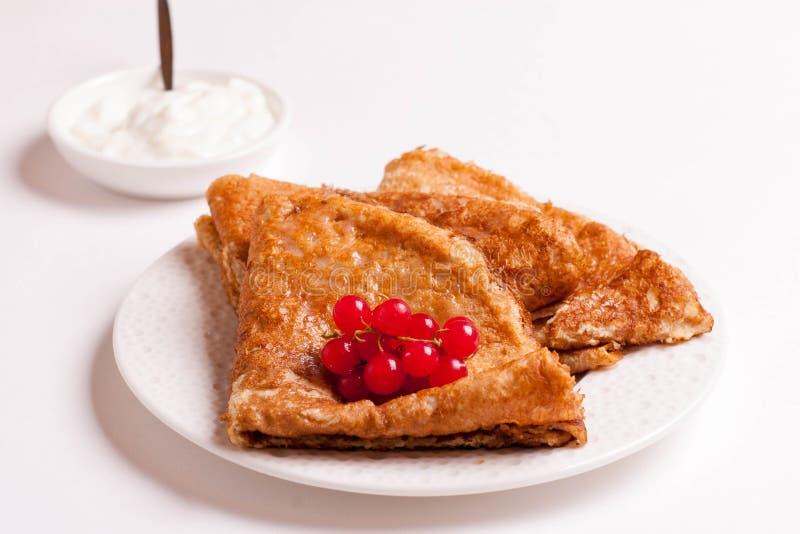 Crêpes avec les groseilles rouges et la crème sure d'un plat d'isolement images stock
