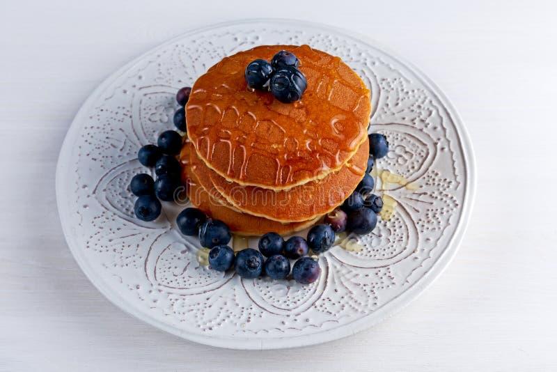 Crêpes avec les myrtilles et le sirop de miel du plat blanc image stock