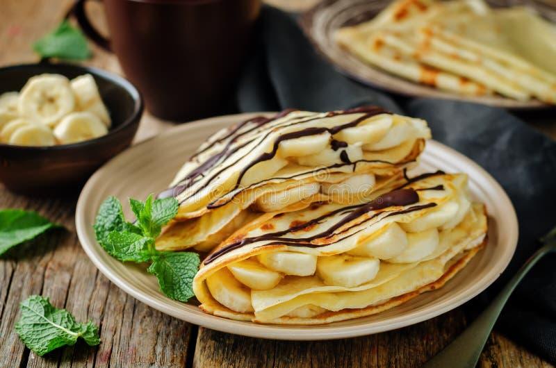 Crêpes avec les slaces frais de banane et le chocolat foncé images libres de droits