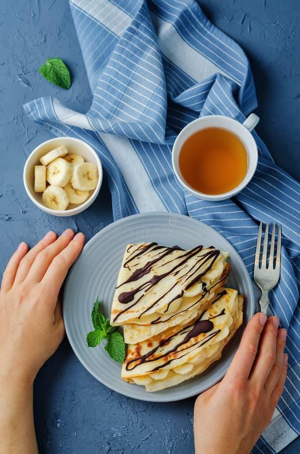 Crêpes avec les slaces frais de banane et le chocolat foncé photo stock