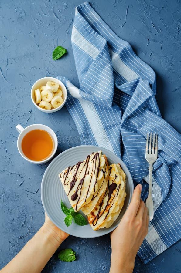 Crêpes avec les slaces frais de banane et le chocolat foncé photo libre de droits