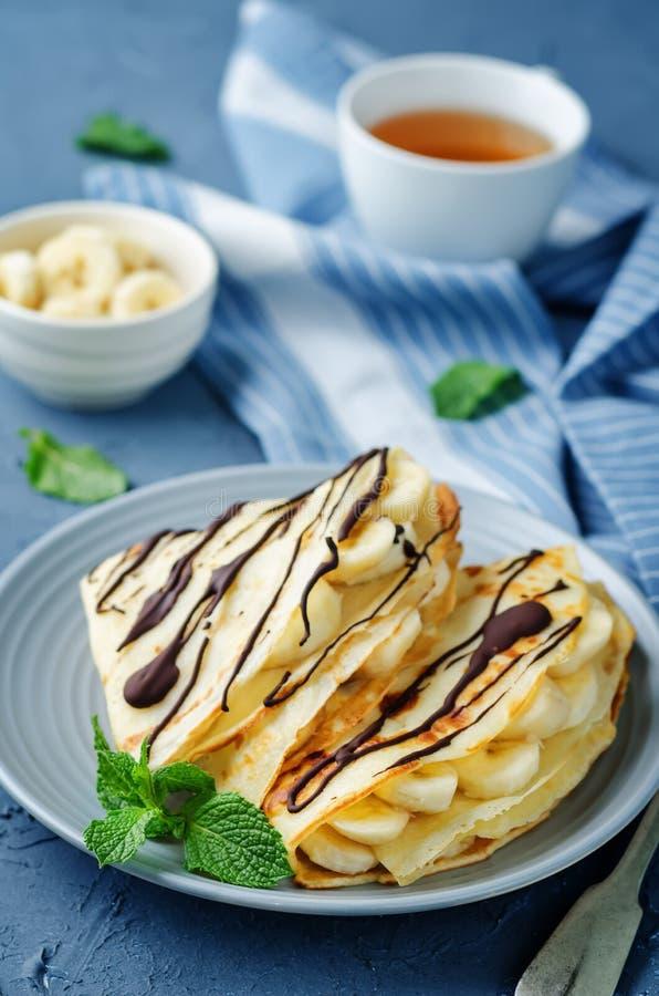 Crêpes avec les slaces frais de banane et le chocolat foncé photos stock