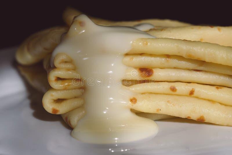 Crêpes d'un plat versé avec du lait condensé photographie stock libre de droits