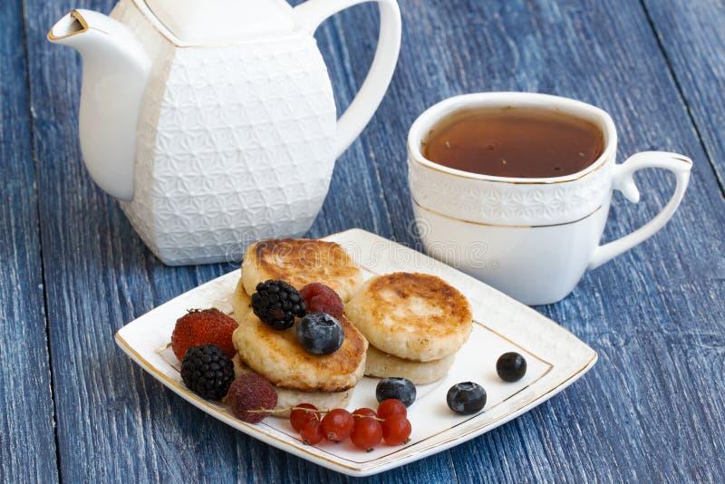 Crêpes de fromage blanc sur le fond bleu Syrniki avec les baies et la crème sure fraîches Nourriture faite maison Crêpes avec image stock