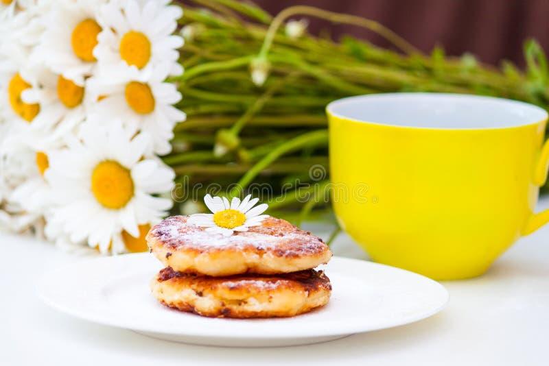 Crêpes de fromage blanc, syrniki avec des camomilles D?jeuner gastronome photo stock