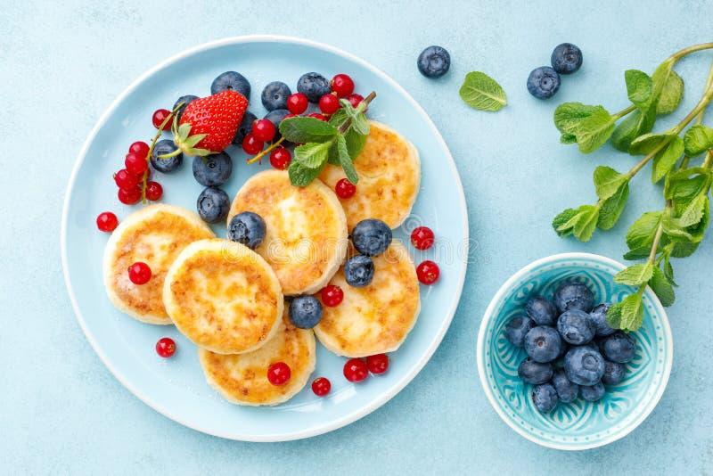 Crêpes de fromage blanc, syrniki avec les baies fraîches pour le petit déjeuner photos libres de droits