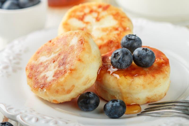 Crêpes de fromage blanc, syrniki, beignets de lait caillé avec les baies fraîches myrtille et miel dans un plat blanc image libre de droits