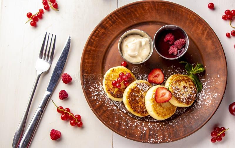 Crêpes de fromage blanc, syrniki ukrainien traditionnel fait maison de plat avec de la sauce à baie et crème sure d'un plat brun  image libre de droits