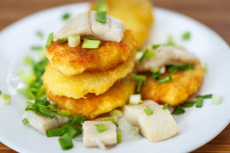 Crêpes de pomme de terre avec les harengs et l'oignon image stock