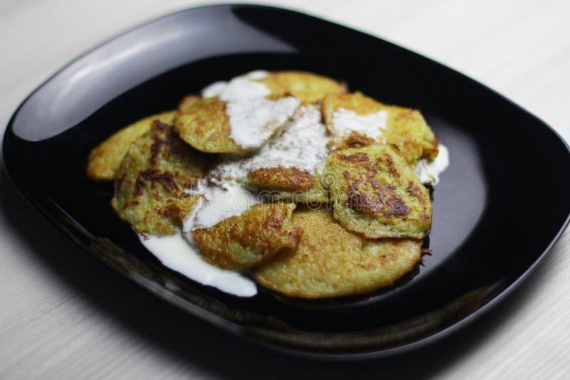Crêpes de pomme de terre avec la crème sure d'un plat noir images stock