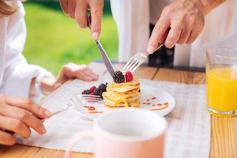 Crêpes de soin aimantes de coupe de mari avec les fruits et le miel sur le dessus pour son épouse image libre de droits