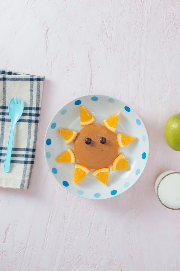 Crêpes drôles avec l'orange pour le petit déjeuner d'enfants photographie stock