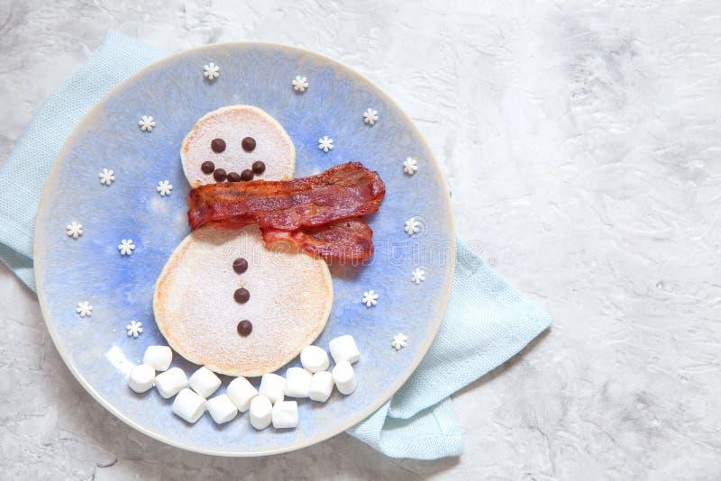 Crêpes drôles de petit déjeuner de matin de Noël de bonhomme de neige pour des enfants photographie stock libre de droits
