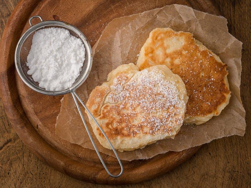 Crêpes faites maison avec du sucre en poudre sur la table en bois photos stock
