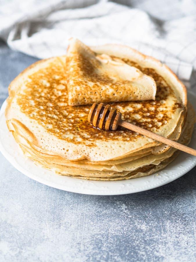 Crêpes faites maison russes de levure de pile du plat blanc, cuillère en bois de miel sur la table grise Crêpes traditionnelles d photos stock