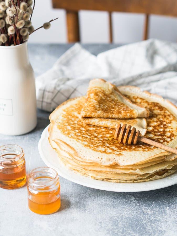 Crêpes faites maison russes de levure de pile du plat blanc, de la cuillère en bois de miel et du miel dans des pots sur la table photos stock