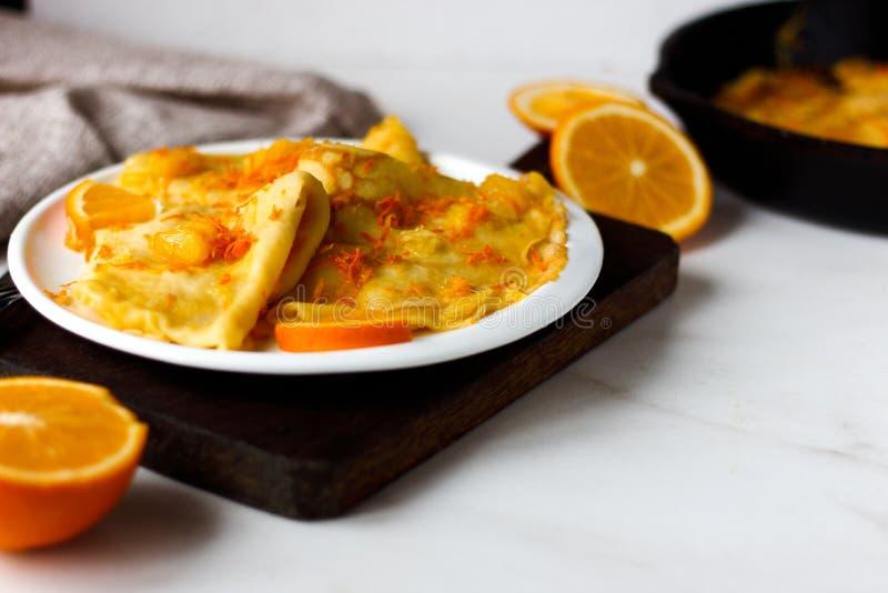 Crêpes françaises traditionnelles Suzette avec de la sauce orange du plat blanc image libre de droits