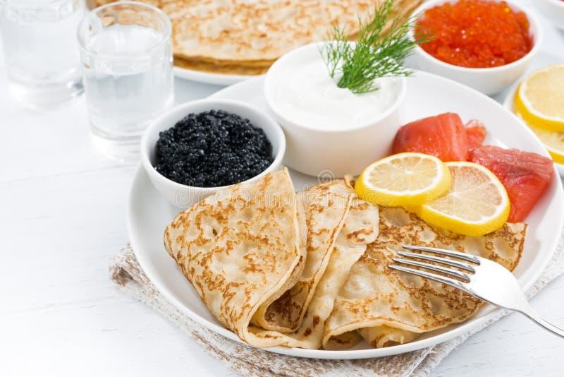Crêpes russes traditionnelles avec le caviar et les poissons salés sur la table images libres de droits