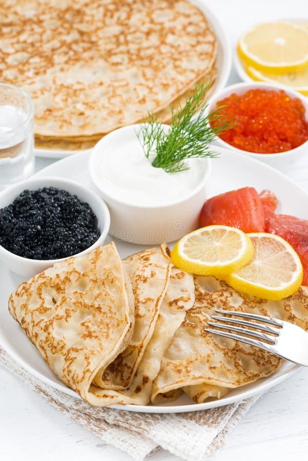 Crêpes russes traditionnelles avec le caviar et les poissons salés, verticaux photographie stock