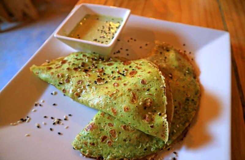 Crêpes savoureuses d'épinards avec de la sauce à moutarde verte servie sur le Tableau en bois photos stock
