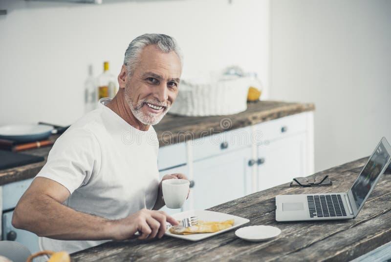 Crêpes savoureuses mangeuses d'hommes de sourire pour le petit déjeuner photographie stock libre de droits
