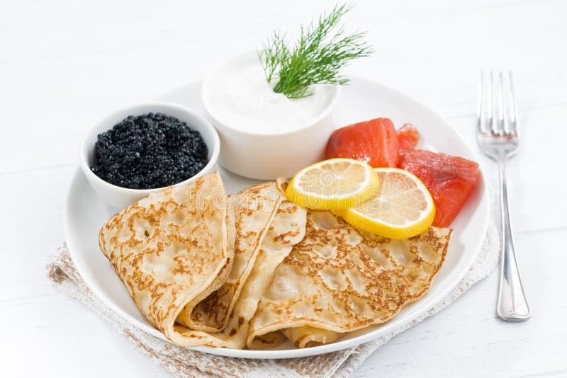 Crêpes traditionnelles avec les poissons, la crème sure et le caviar photos libres de droits