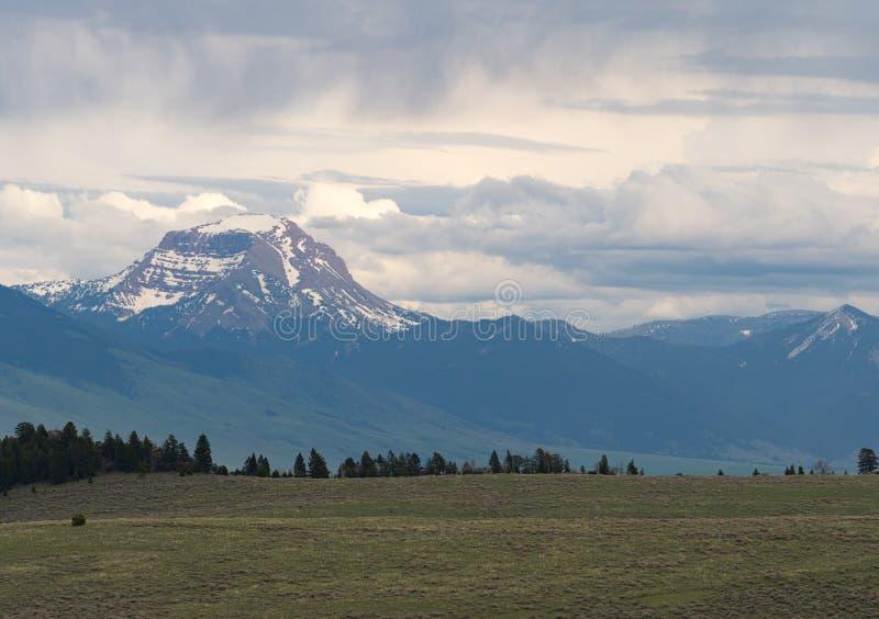 Crête de montagne couverte par neige avec la prairie photos stock