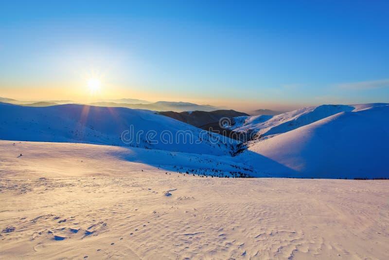 Crêtes de montagne couvertes de neige et de glace, sur lesquelles tombe l'ombre bleue, contre le ciel bleu Jour givré, scène hive photos stock