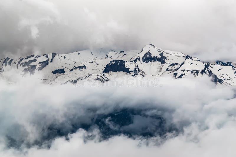 Crêtes neigeuses de montagne couvertes de nuages épais, vue mystérieuse de la montagne images stock