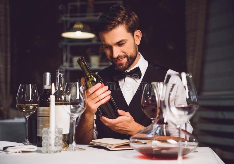 Crítico del vino que sostiene la botella de bebida del escarlata con sonrisa fotografía de archivo