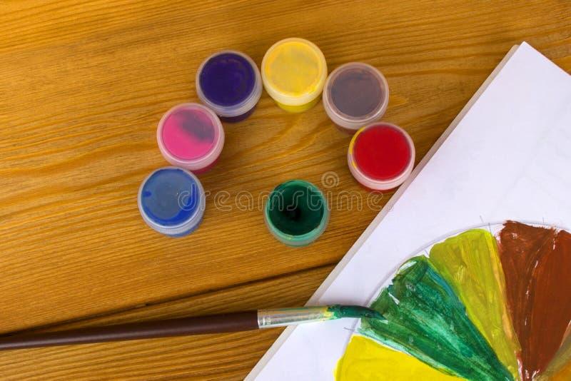 Cr?ativit? du ` s d'enfants Peintures de dessin 12 couleurs de peinture Palette de couleur Peintures sur un fond en bois Peinture photo libre de droits