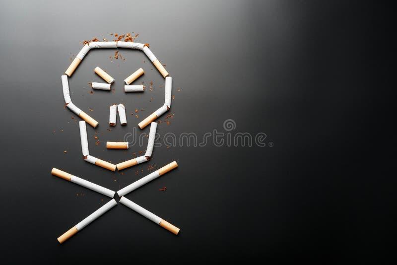 Cr?neo de los cigarrillos en un fondo negro El concepto de matanzas que fuman Hacia el concepto de fumar como h?bito mortal, imagen de archivo libre de regalías