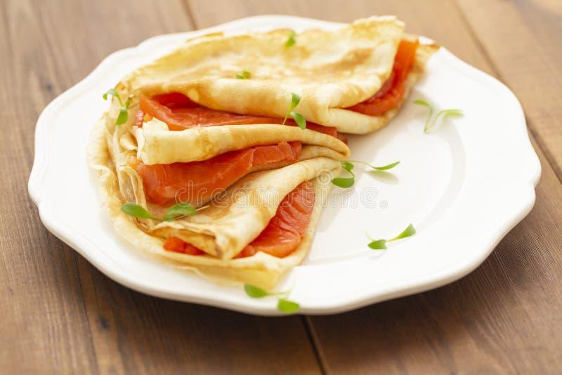 Cr?pe con il salmone affumicato su un piatto bianco Prima colazione deliziosa e sana immagini stock libere da diritti