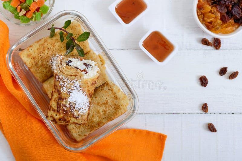 Cr?pes sensibles d?licieuses avec le fromage blanc et les raisins secs dans un conteneur en verre sur un fond en bois blanc image stock