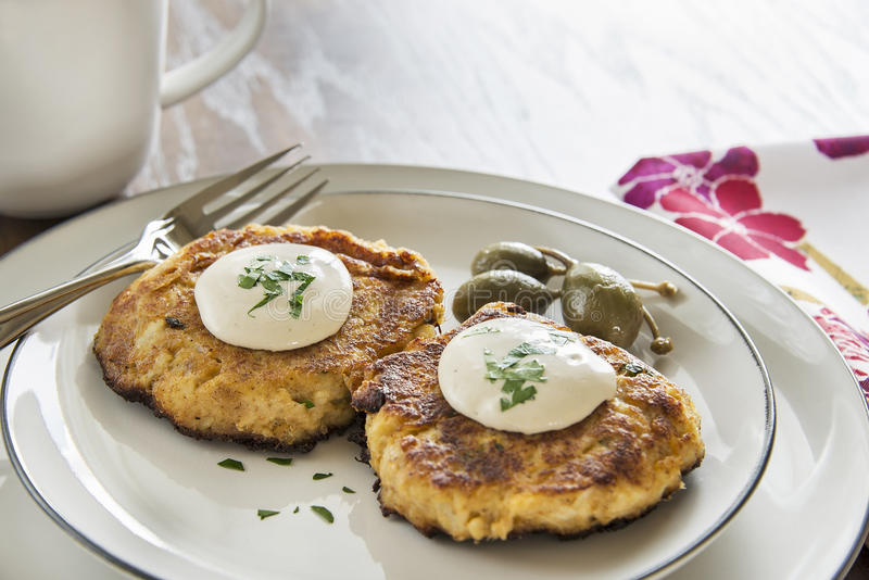 Crab cakes with creamy mustard sauce. A pair of delcious crab cakes topped with a creamy mustard sauce and parsley are accompanied by caper berries stock photos