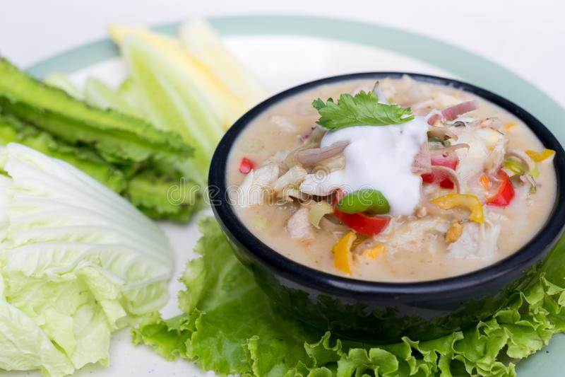 Crab dip with coconut milk and vegetables in bowl stock photo