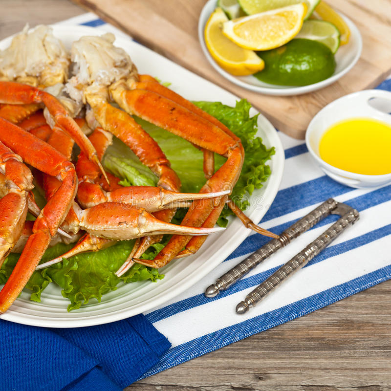 Crab legs. Snow Crab legs with fresh lemon slices and butter sauce. Selective focus on claw stock images