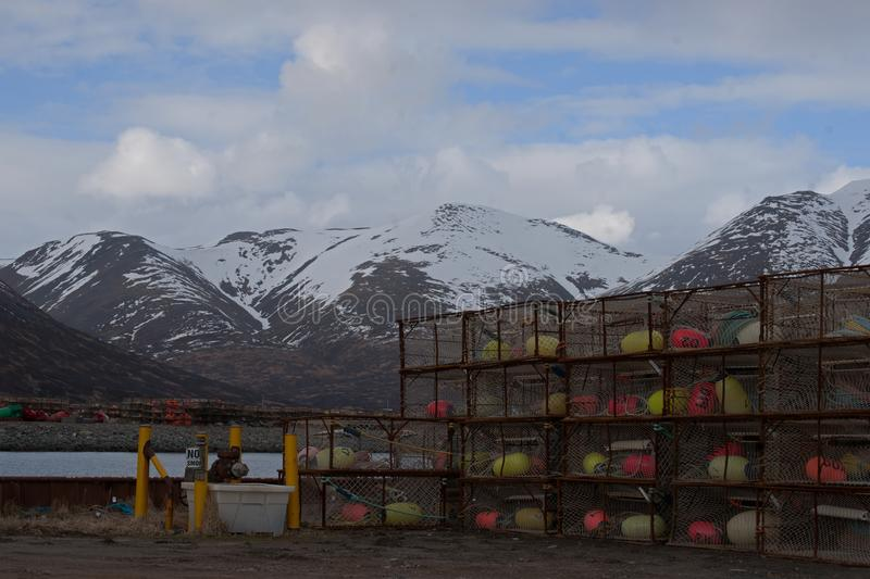 Crab Lobster Pots King Cove Alaska. Stacks of Crab and Lobster Pots stored at King Cove Alaska harbor with snow covered mountains in background stock image