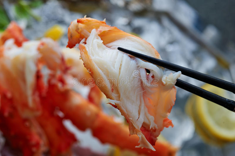 Crab meat. A closeup of chopsticks holding crab meat royalty free stock photo