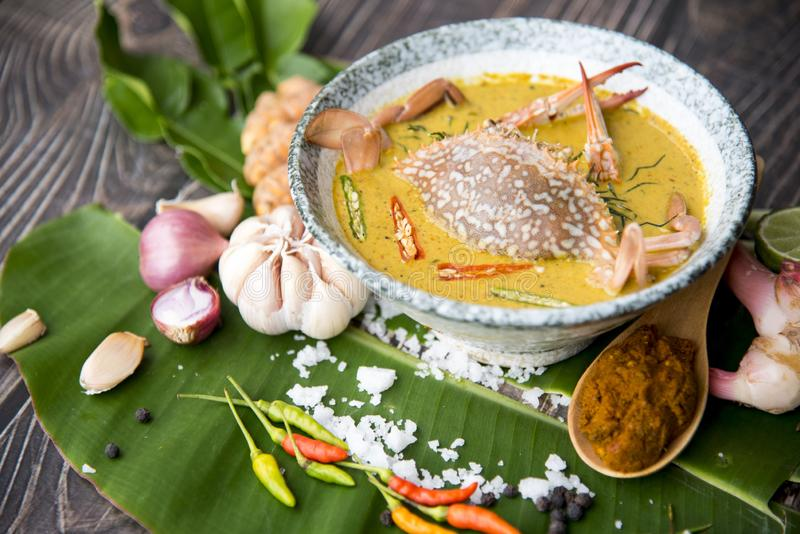 Crab meat coconut milk curry, in bowl and ingredient of Thai Red curry paste on brown wooden background Thai food / Select focus i stock image