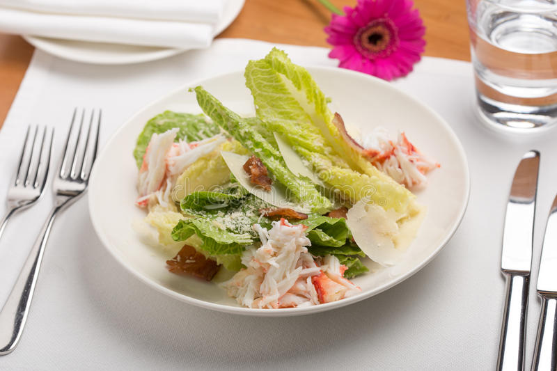 Crab salad. With bread, flower and water on wooden table royalty free stock photos