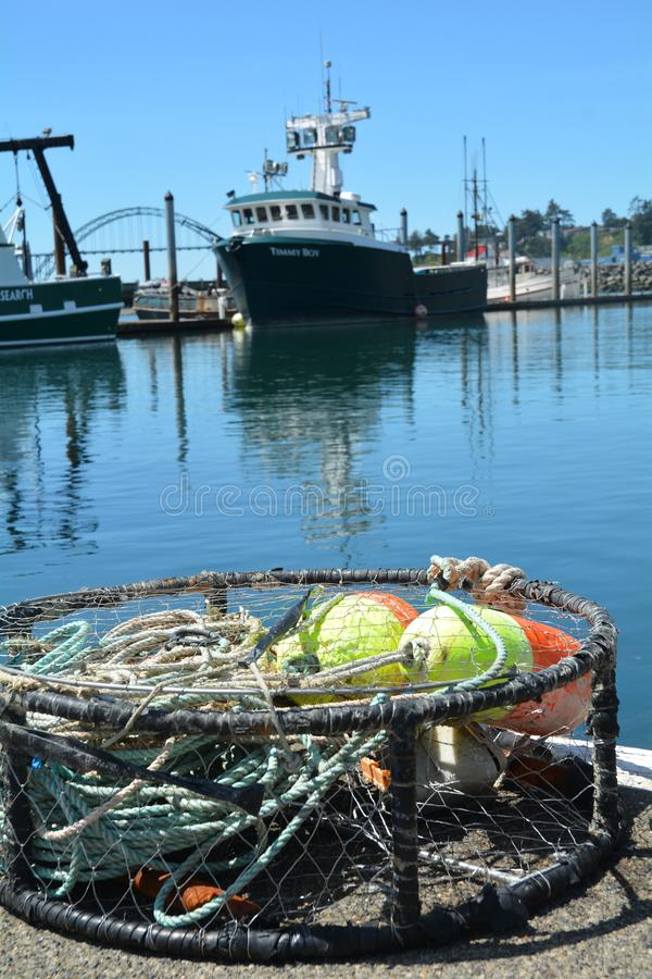 Crab trap and fishing boat Timmy Boy in Newport, Oregon. This is a crab trap on the wharf in Newport, Oregon`s Yaquina Bay with the fishing boat `Timmy Boy` in royalty free stock photography