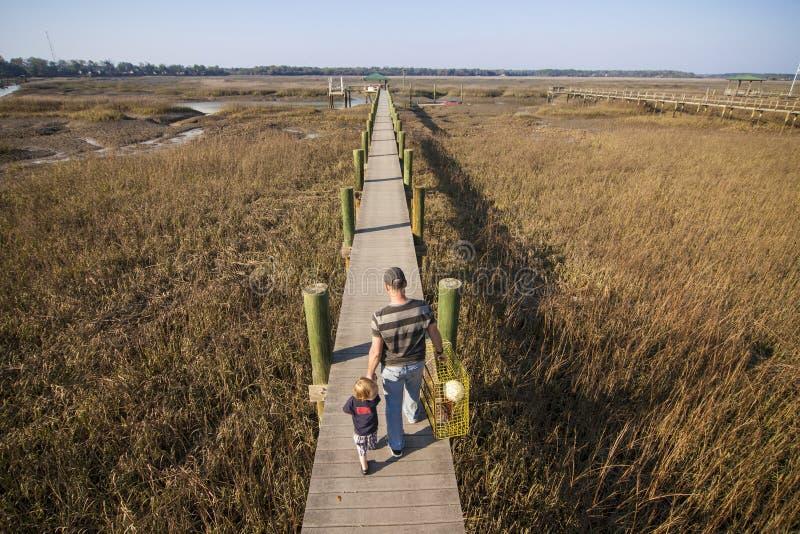 Crabbing отца и сына идя совместно стоковые фотографии rf