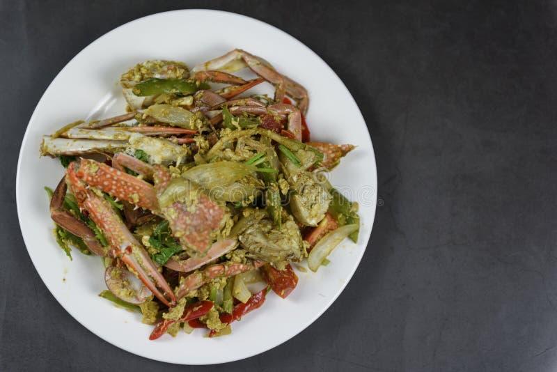 Crabe fait sauter à feu vif avec le curry du plat blanc, d'isolement sur le fond noir, protection thaïlandaise Pong Karee de Bu d photos libres de droits