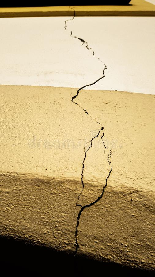 Crack on the building wall surface over the doors extending all the way to the window after an earthquake disaster. Strike happened royalty free stock images