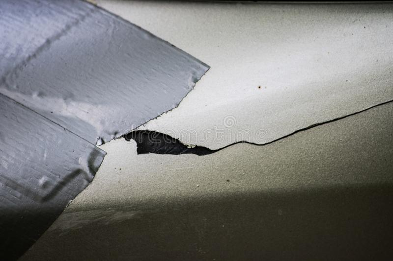 The crack in the car body is sealed with an industrial adhesive tape close. Up stock photos