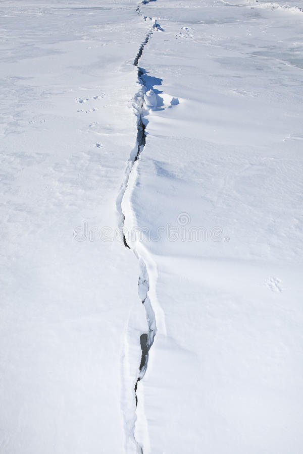 Crack in the ice covered with snow. Even in winter sunlit royalty free stock photos