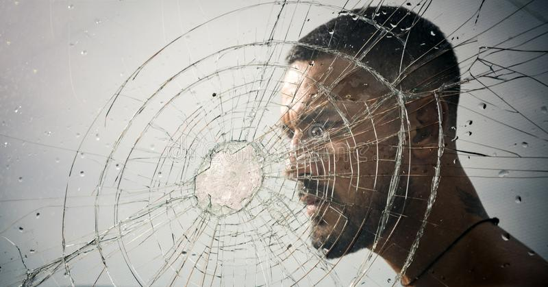 Crack. macho man behind crushed glass. anger. destruction. crush test. theft. emotional discharge. bullet hole in glass royalty free stock image